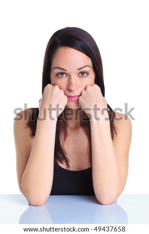 Woman leaning on her hands looking towards camera with a serious expression on her face, white background. - stock photo