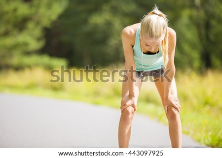 Woman leaning on knees and catch breath after stamina workout - stock photo