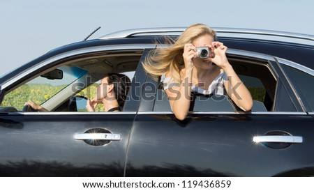 Woman leaning out of the window of a car photographing with a compact digital camera