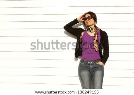 Woman leans against building. - stock photo