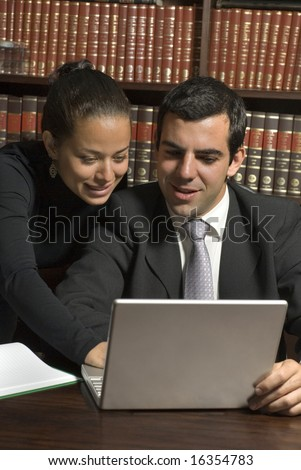 Woman leans over man's shoulder. Man is wearing a suit and they are both looking at a laptop. Vertically framed photo. - stock photo