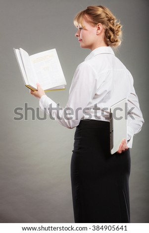 Woman learning with book holding ebook reader behind back. Choice between modern educational technology and traditional way method. Girl holding digital tablet pc and textbook. Contemporary education.