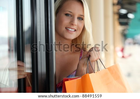 Woman leaving a store with shopping bags - stock photo