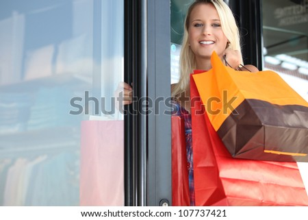 Woman leaving store with shopping bags - stock photo