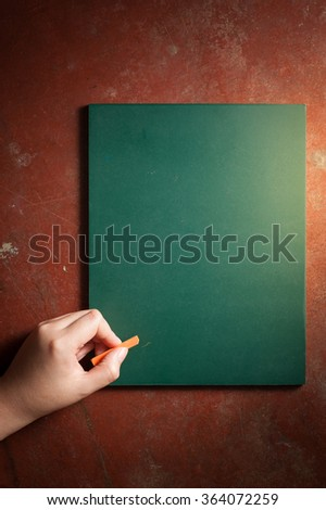 Woman left hand writing on small black board in green color with blank space for text or message with low key scene