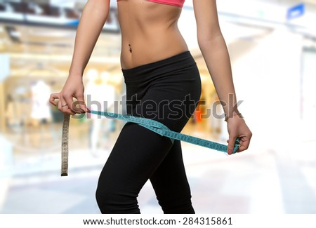 Woman leg close up with a measurement scale. Over shopping center background - stock photo