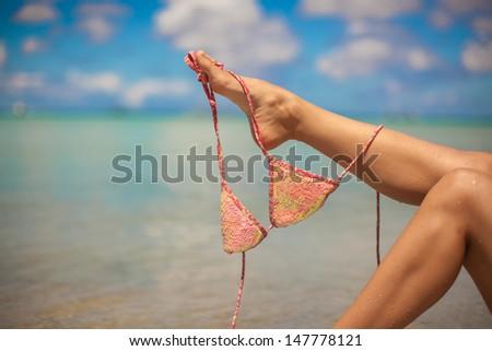 Woman leg holding pink bra isolated on exotic background - stock photo