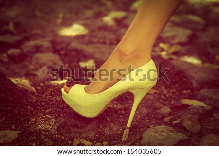 woman leg in high heel shoe lean on cobble street retro colors - stock photo