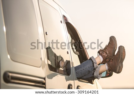Woman legs against evening sky background out of car stacking. Freedom car travel concept - stock photo