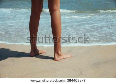 Woman legs and feet walking on the sand of the beach with the sea water in the background summer