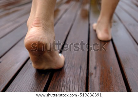 woman legs and-feet walking on the wood floor after rain