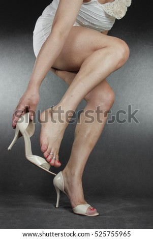 Woman legs and feet wearing  dress putting on heels  over grey background