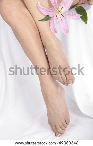 Woman legs and feet with flower isolated over white - stock photo