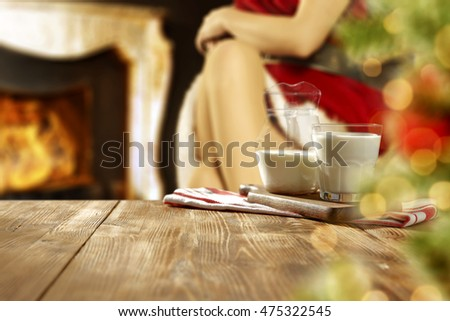 woman legs and wooden table and fireplace