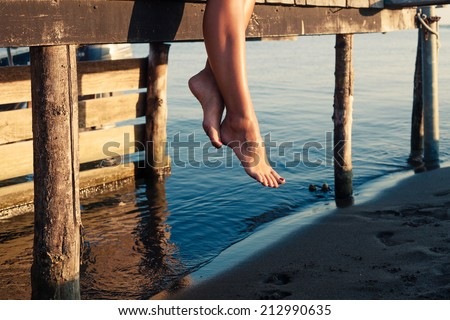 woman legs as she sitting on old wooden dock at sea shore - stock photo