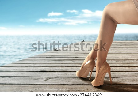 woman legs heels and wooden pier with blue sea and sky