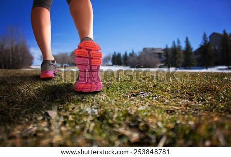 woman legs hiking hill with thawing snow on a sunny afternoon with a drama filter (shallow depth of field)