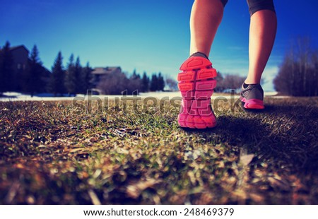 woman legs hiking hill with thawing snow on a sunny afternoon with retro instagram filter (shallow depth of field) - stock photo