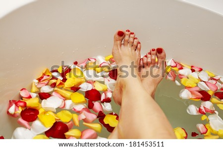 Woman legs in bath with rose petals - stock photo
