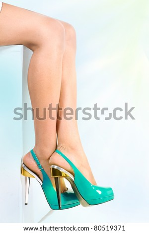 Woman legs in blue high heels shoes, over blue sunny sky background, woman is sitting relaxed, healthy legs concept