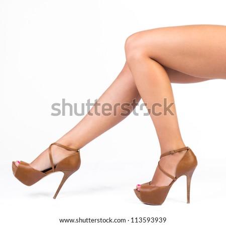 woman legs in brown high heels shoes, studio shot - stock photo