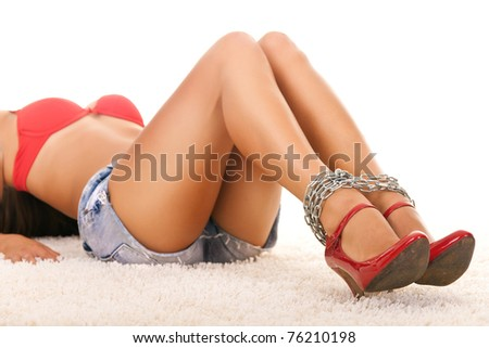woman legs in chains with red high heels - stock photo