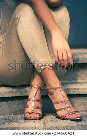 woman legs in high heel golden sandals and pants sit on stairs, outdoor shot, close up - stock photo