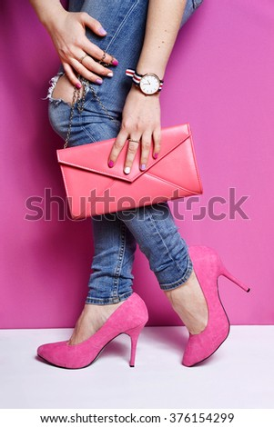Woman legs in jeans with pink handbag and high heels shoes . Pink background . Trendy accessories watch - stock photo