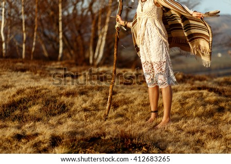 woman legs in native indian american boho dress walking in windy sunny evening mountains, holding feathers - stock photo