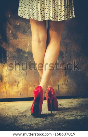 woman legs in red high heel shoes and short skirt outdoor shot against old metal door - stock photo