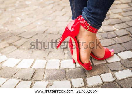 woman legs in red high heel shoes outdoor shot on cobble street - stock photo