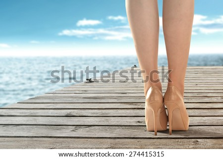 woman legs in shoes and wooden gray pier with sea and sky