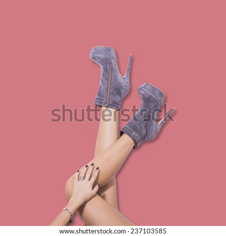 woman legs in velour high heel platform ankle boots lean on pastel pink wall upside down - stock photo