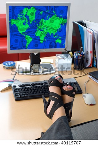 woman legs on office desk in front of computer with money screen - stock photo