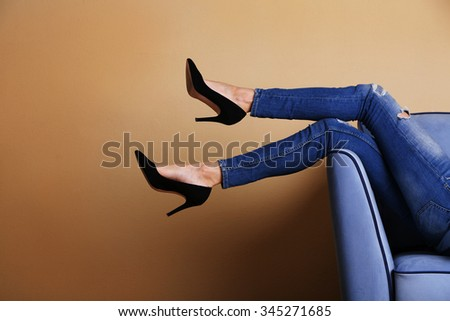Woman legs on sofa with stylish shoes in room  - stock photo