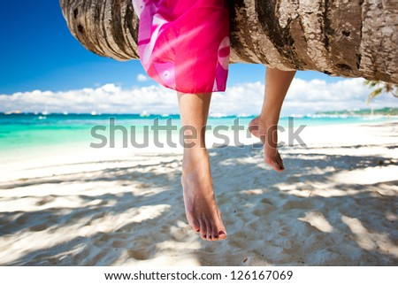 Woman legs on the beach, relaxing on palm tree