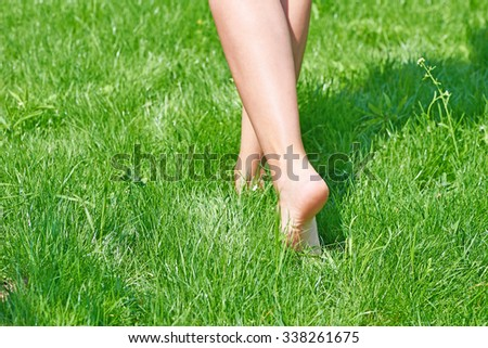 Woman legs on the green grass