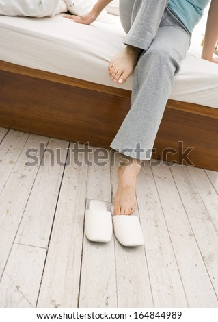 woman legs raised up high and arms under her head lying on bed in bedroom - stock photo