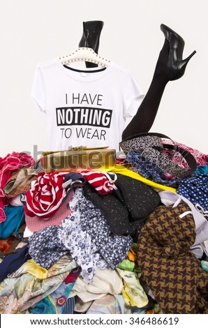 Woman legs reaching out from a big pile of clothes with a t-shirt saying nothing to wear. Girl buried under an untidy cluttered wardrobe. Woman in high heels and to much shopping. Shopaholic girl. - stock photo