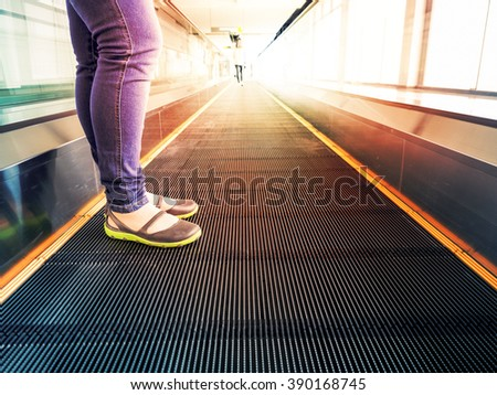 woman legs standing in escalator in interior business building