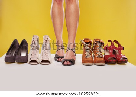 woman legs surrounded by the shoes  on yellow - stock photo