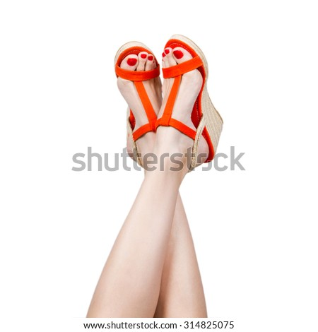 Woman legs wearing a pair of sandals, isolated on white - stock photo