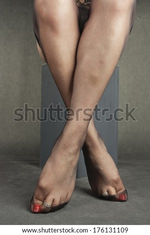 Woman legs wearing black hold-ups over grey background - stock photo