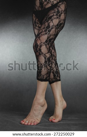 Woman legs wearing black lace leggins over grey background - stock photo