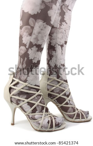 Woman legs wearing heels and tights over white background - stock photo