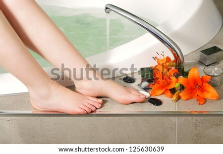 woman legs with flowers in spa salon.shallow DOF - stock photo