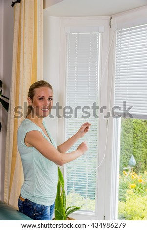 woman lets down blinds