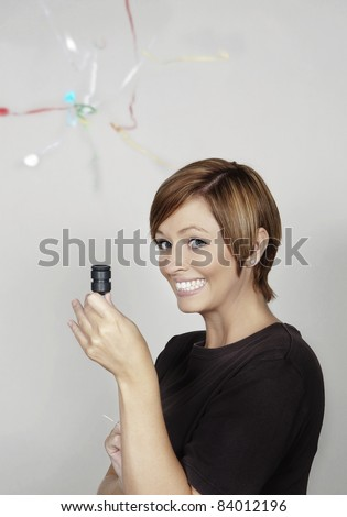 woman letting of a party popper - stock photo