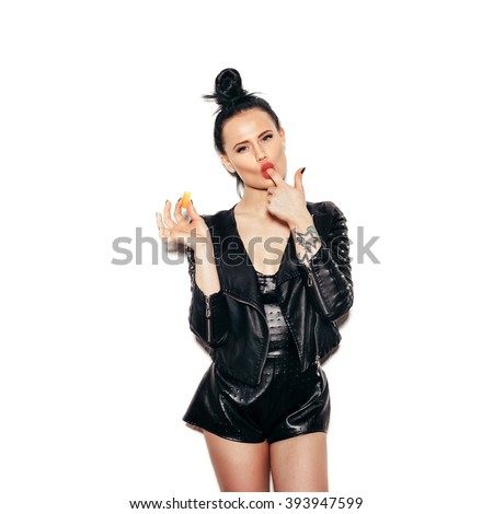 Woman licking finger enjoying candy. Swag girl posing against white background, not isolated - stock photo