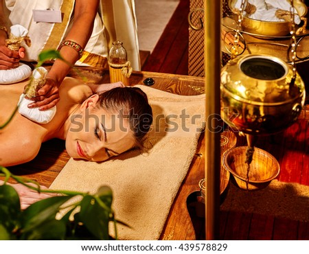 Woman lie on stomach having ayurvedic massage with pouch of rice. Shirodhara pot for head massage on foreground. - stock photo